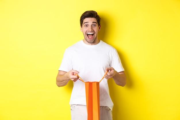 Zaskoczony facet otwiera pięścią torbę na zakupy, wygląda na podekscytowanego i szczęśliwego w kamerze, stojąc na żółtym tle