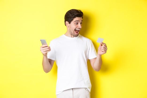 Zaskoczony facet trzyma smartfon i kartę kredytową, zakupy online w czarny piątek, stojąc na żółtym tle.