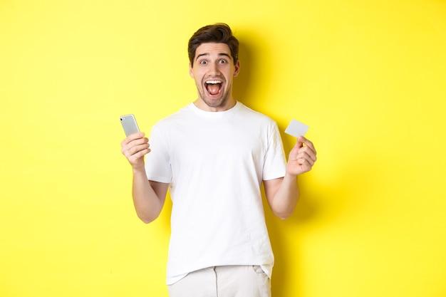 Zaskoczony facet trzymający smartfona i kartę kredytową, zakupy online w czarny piątek, stojący na żółtym tle