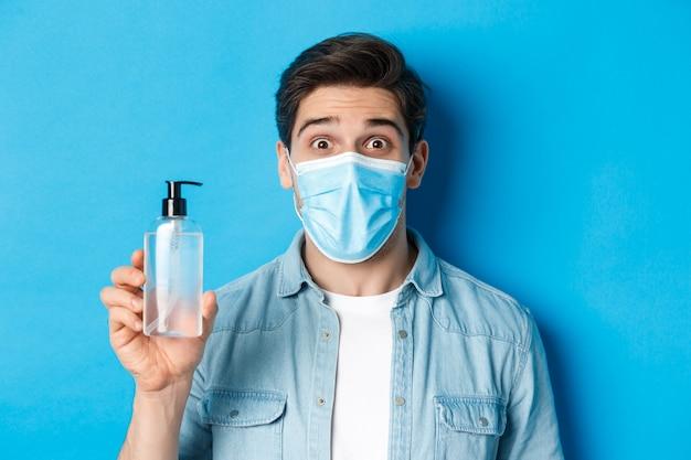 Zaskoczony facet w masce medycznej, trzymając butelkę odkażacza do rąk, unosząc zdumiony brwi, stojąc nad niebieską ścianą