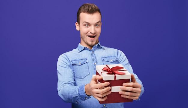 Zaskoczony facet w niebieskiej dżinsowej koszuli i okrągłych okularach z dwoma prezentami w ręku