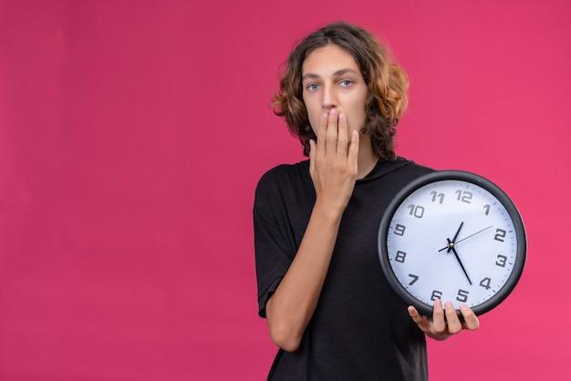 Zaskoczony facet z długimi włosami w czarnej koszulce trzyma zegar ścienny i zakrył usta ręką na różowym tle