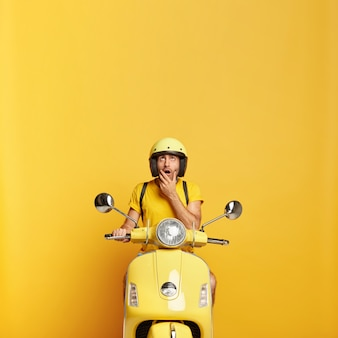 Zaskoczony facet z hełmem jazdy żółty skuter