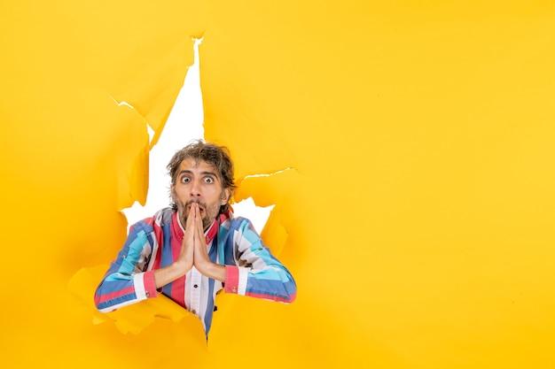Zaskoczony i emocjonalny młody człowiek pozuje na rozdartym żółtym tle dziury w papierze