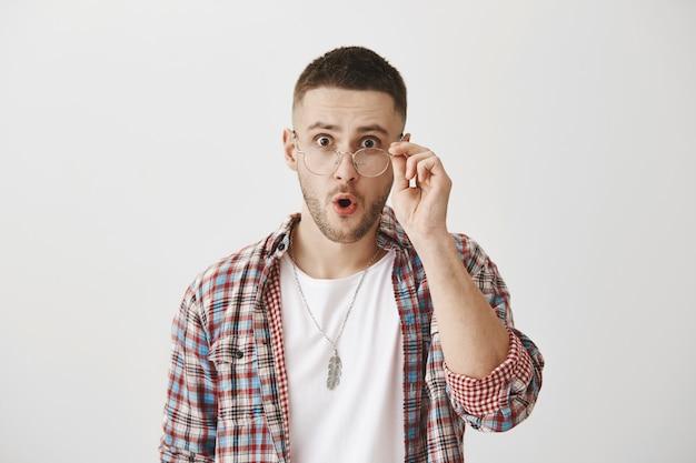 Zaskoczony i pod wrażeniem młody chłopak w okularach pozowanie