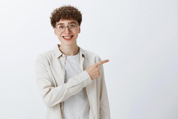 Zaskoczony i pod wrażeniem nastoletni chłopak pozujący pod białą ścianą