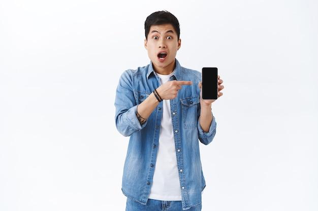 Zaskoczony i podekscytowany azjata pokazujący profil znajomych osoby dopasowanej do niego w aplikacji randkowej, przytłoczony i zszokowany, wskazujący smartfonem