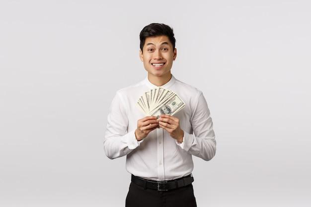Zaskoczony i podekscytowany młody szczęśliwy azjatycki facet w oficjalnym stroju, pokazujący dużo pieniędzy, dużą gotówkę i uśmiechnięty zdziwiony, wygrywający na loterii, otrzymuje nagrodę finansową z radością
