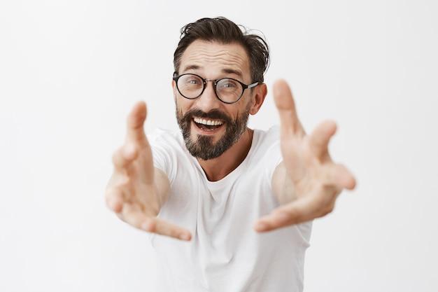 Zaskoczony i szczęśliwy brodaty dojrzały mężczyzna w okularach pozowanie