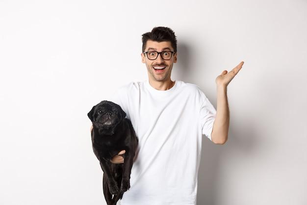Zaskoczony i szczęśliwy właściciel psa trzymający słodkiego czarnego mopsa, podnoszący rękę zdumiony, patrzący na aparat zadowolony, stojący na białym tle