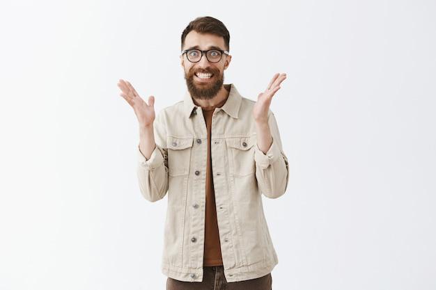 Zaskoczony i wdzięczny brodaty mężczyzna w okularach pozuje na białej ścianie