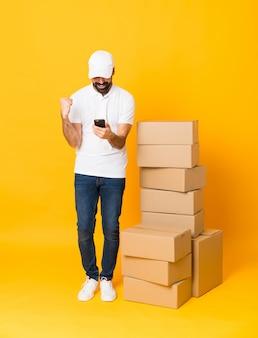 Zaskoczony i wysłanie wiadomości pełna długość człowieka dostawy wśród pudeł nad izolowaną żółtą ścianą
