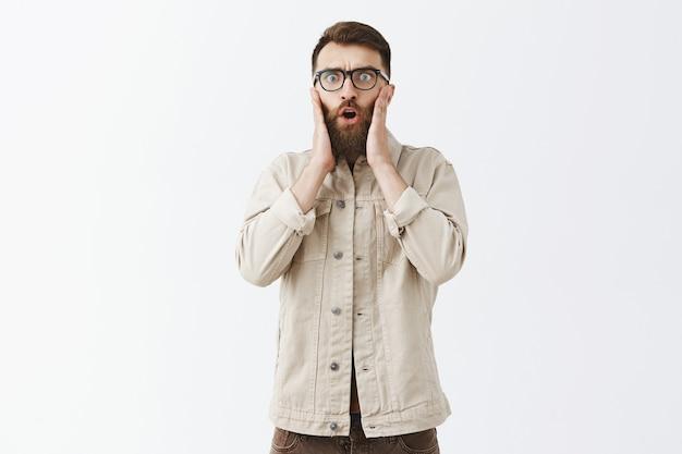 Zaskoczony i zdumiony brodaty mężczyzna w okularach pozujący na białej ścianie