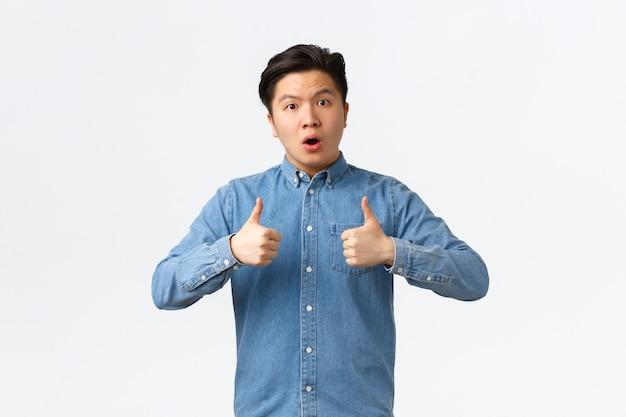 Zaskoczony i zdumiony przystojny azjatycki facet pokazujący kciuki do góry i wyglądający na zdumionego, gratuluje osobie doskonałej pracy, nieoczekiwanej dobrej pracy, mówi dobrze wykonanej, biała ściana
