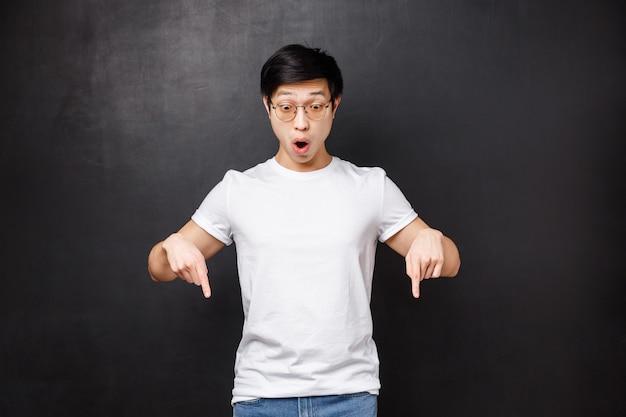 Zaskoczony i zdziwiony bezmyślny azjatycki facet widzi coś szokującego i niesamowitego, wskazującego w dół, składane usta rozbawione powiedzą wow, wpatrujące się w fajny produkt,