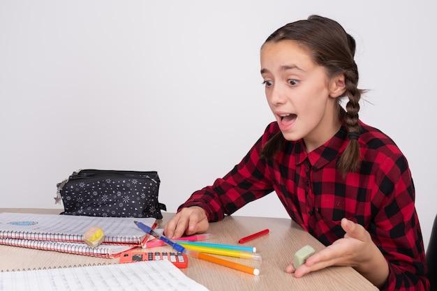Zaskoczony i zły dziewczyna robi zadanie domowe w szkole