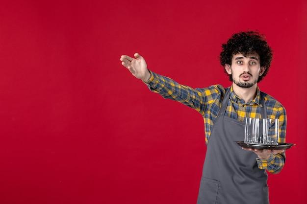 Zaskoczony kelner z kręconymi włosami trzymający tacę w okularach wskazujący coś na pojedyncze czerwone tło