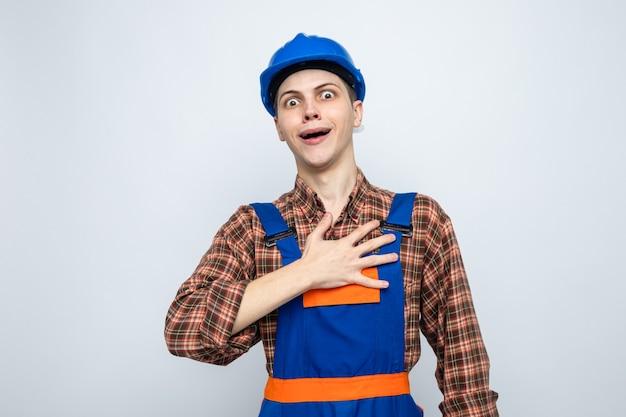 Zaskoczony, kładący dłoń na sercu, młody budowniczy mężczyzna ubrany w mundur