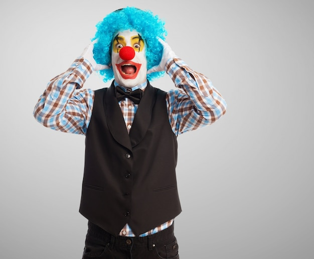Zaskoczony klaun z rękami na głowie