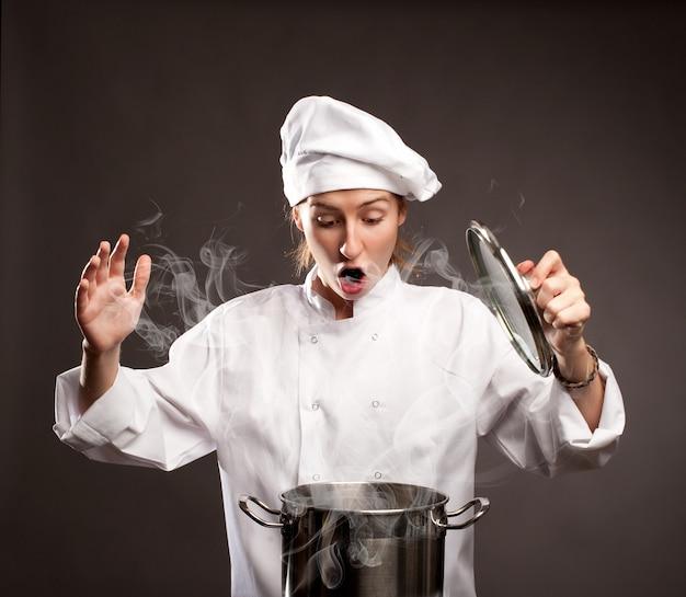 Zaskoczony kobieta kucharz trzyma pokrywkę