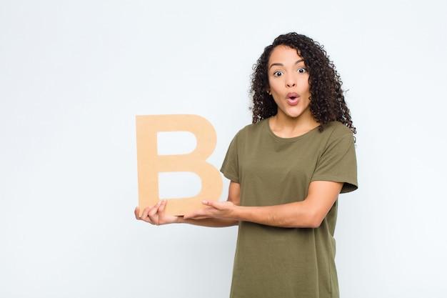 Zaskoczony, kobieta trzyma literę b alfabetu, aby utworzyć słowo