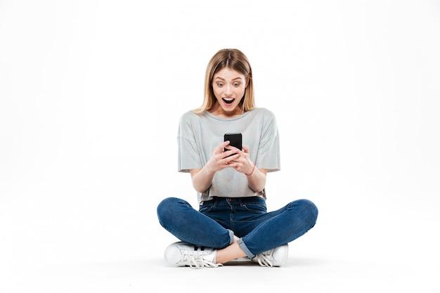 Zaskoczony, kobieta za pomocą smartfona