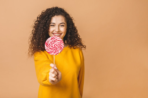 Zaskoczony, kręcone dziewczyna jedzenie lizaka. piękno wzorcowa kobieta trzyma różowego słodkiego kolorowego lizaka cukierek, odizolowywającego na beżowym tle.