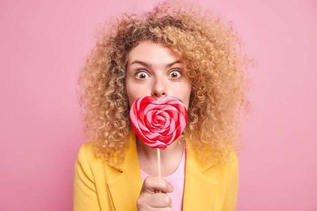 Zaskoczony kręcone włosy młoda kobieta obejmuje usta cukierkiem w kształcie serca ma słodycze posiada lizaka ubrany w żółtą kurtkę na białym tle nad różową ścianą. dużo cukru nie jest w porządku. słodkie smakołyki