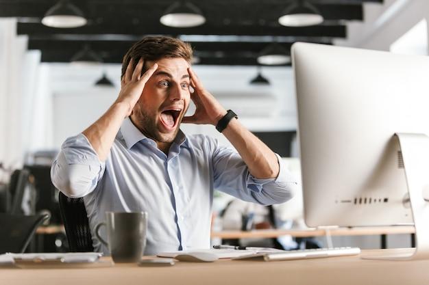 Zaskoczony krzyczący biznesmen przy użyciu komputera i trzymając głowę, siedząc przy stole w biurze