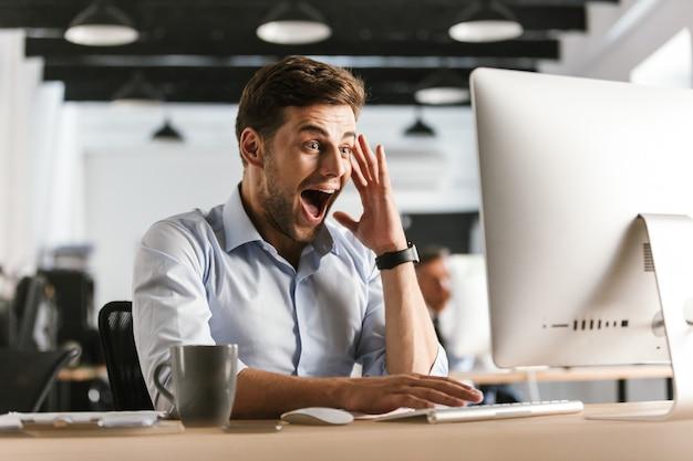 Zaskoczony krzyczący biznesmen przy użyciu komputera siedząc przy stole w biurze