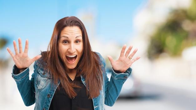 Zaskoczony krzyczy kobieta z rękami podniesionymi do góry