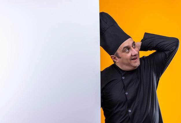 Zaskoczony kucharz w średnim wieku w mundurze szefa kuchni kładąc rękę na głowie trzymając białą ścianę na żółtym tle z miejsca na kopię
