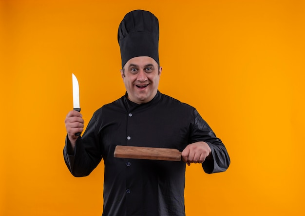 Zaskoczony kucharz w średnim wieku w mundurze szefa kuchni, trzymając nóż i deskę do krojenia na żółtym tle z miejsca na kopię