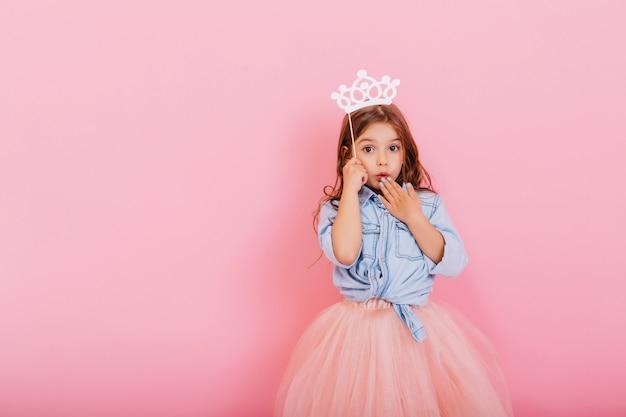 Zaskoczony, ładna młoda dziewczyna w tiulowej spódnicy z koroną na głowie, wyrażając na białym tle na różowym tle. niesamowita śliczna mała księżniczka na karnawale. miejsce na tekst
