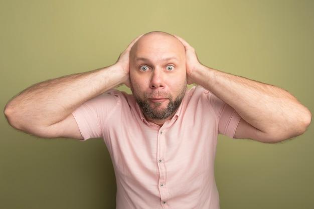 Zaskoczony łysy mężczyzna w średnim wieku ubrany w różową koszulkę złapał głowę odizolowany na oliwkowej zieleni