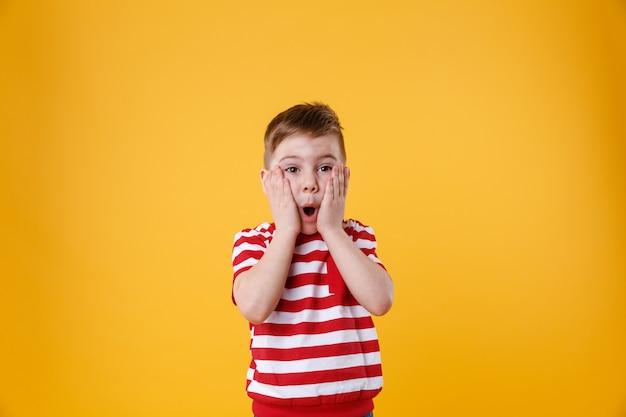 Zaskoczony małe dziecko z rękami na twarzy