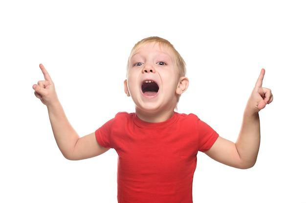 Zaskoczony mały blond chłopiec w czerwonej koszulce stoi i wskazuje palcami wskazującymi w górę