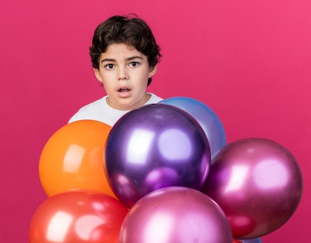 Zaskoczony mały chłopiec stojący za balonami odizolowanymi na różowej ścianie