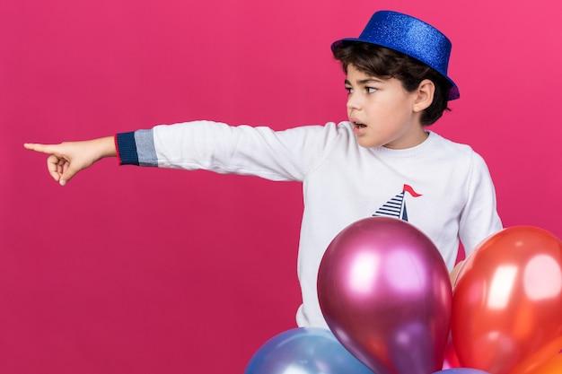 Zaskoczony mały chłopiec w niebieskiej imprezowej czapce stojący za balonami wskazuje bok na różowej ścianie