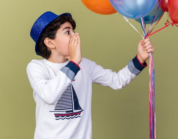 Zaskoczony mały chłopiec w niebieskiej imprezowej czapce, trzymający balony, wołający kogoś