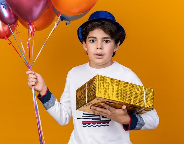 Zaskoczony mały chłopiec w niebieskiej imprezowej czapce, trzymający balony z pudełkiem na białym tle na pomarańczowej ścianie