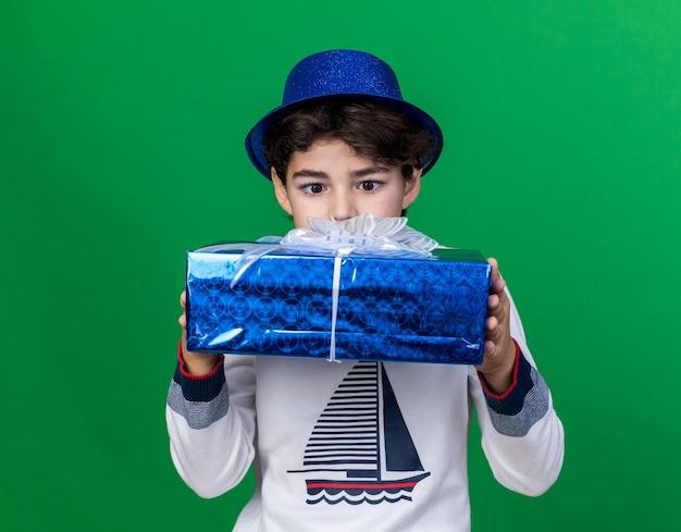 Zaskoczony mały chłopiec w niebieskiej imprezowej czapce, trzymający i patrzący na pudełko na białym tle na zielonej ścianie