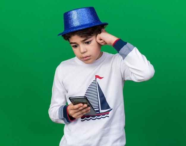 Zaskoczony mały chłopiec w niebieskiej imprezowej czapce, trzymający i patrzący na telefon odizolowany na zielonej ścianie