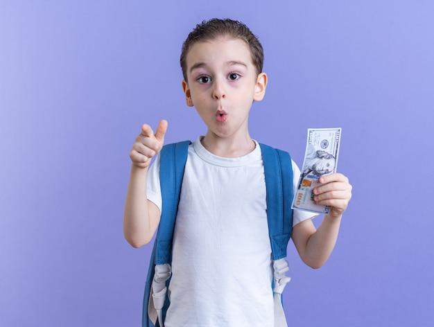 Zaskoczony mały chłopiec w plecaku, trzymający dolara, patrzący i wskazujący na kamerę odizolowaną na fioletowej ścianie