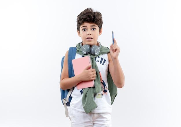 Zaskoczony mały uczeń na sobie tylną torbę i słuchawki, trzymając notebook i podnosząc pióro na białym tle