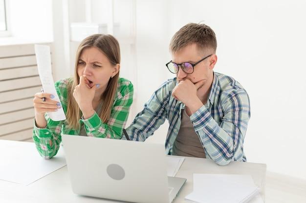 Zaskoczony mąż i żona małżeństwa rozważają rachunki za mieszkanie i tak właśnie jest