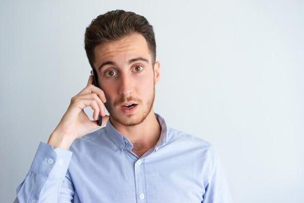 Zaskoczony menedżer przytłoczony rozmową telefoniczną