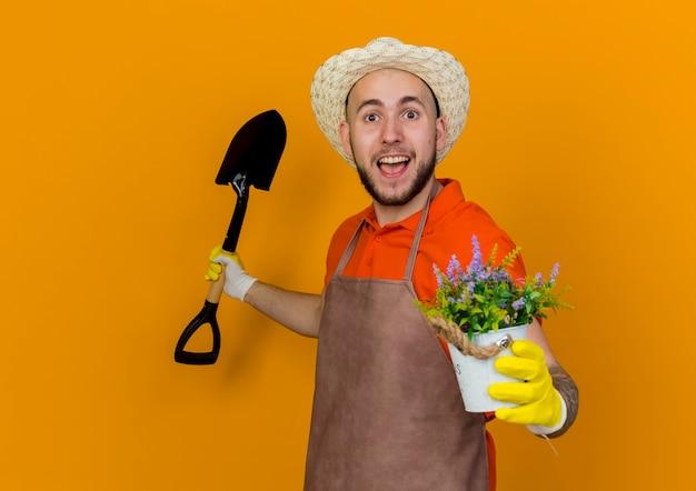 Zaskoczony męski ogrodnik w kapeluszu ogrodniczym i rękawiczkach, trzymając łopatę i kwiaty w doniczce