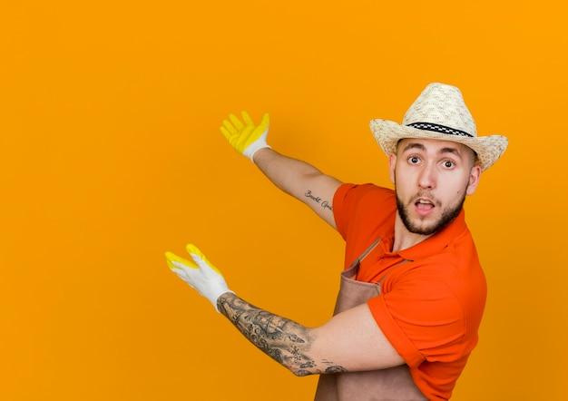 Zaskoczony męski ogrodnik w kapeluszu ogrodniczym i rękawiczkach wskazuje z tyłu dwiema rękami patrząc