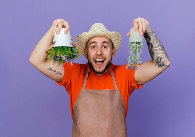 Zaskoczony męski ogrodnik w kapeluszu ogrodniczym trzyma doniczki do góry nogami